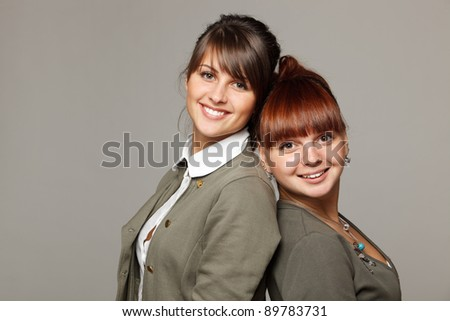 Closeup of two smiling girls standing back to back, over grey background - stock photo