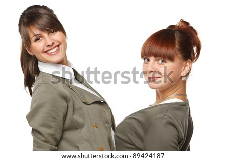 Closeup of two smiling girls standing face to face, over white background - stock photo