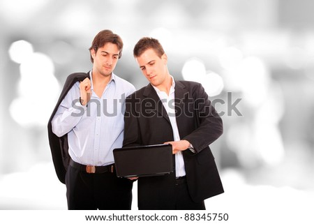 Closeup of two standing looking at a notebook computer in a light and mordern business environement - stock photo