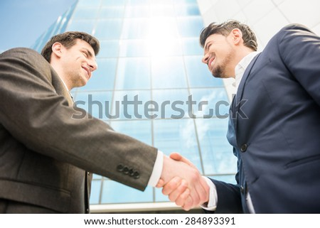 Closeup of two successful smiling business men shaking hands.
