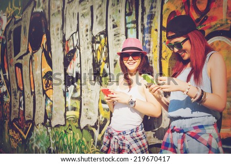 Closeup of two teenage girls with smart phones. Two young women using smartphones against colorful graffiti wall.