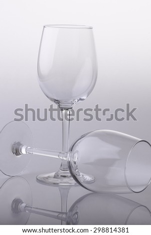 Closeup of two transparent clear crystal empty wine glasses standing and lying isolated on chrome white and grey background, vertical picture - stock photo