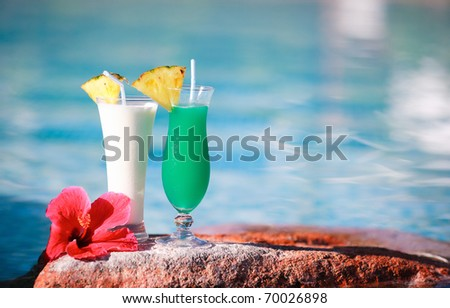 Closeup of two tropical cocktails near water