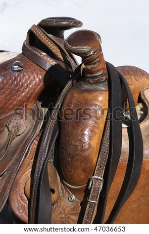 Closeup of two western horse saddles grouped together. Vertical shot. - stock photo