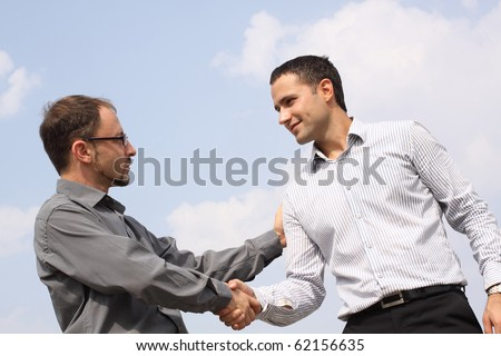 Closeup of two young businessmen shaking hands over a deal on sky background - stock photo