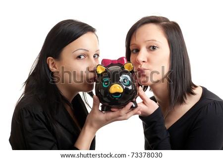 closeup of two young women kissing a piggy bank - stock photo