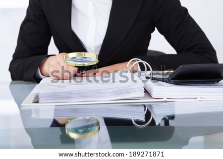 Closeup of uditor scrutinizing financial documents at desk in office - stock photo