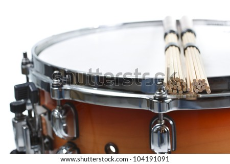 Closeup of unplugged sticks resting on a cherry sunburst colored snare drum, shown only a part of its side and top with the metal rim - isolated on white - stock photo