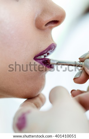 Closeup of unrecognizable adult woman having her lips covered with lips gloss by makeup artist.  Selective focus  - stock photo