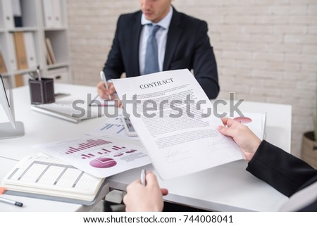 Closeup of unrecognizable business person holding contract and reading it during negotiations meeting with partner, copy space