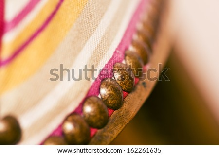 closeup of upholstery tacks on an old traditional wooden chair - stock photo
