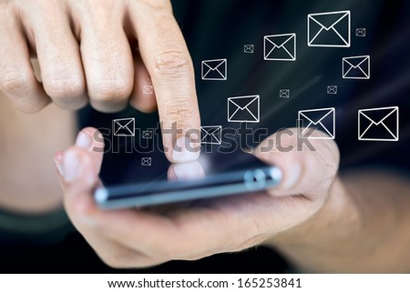 Closeup of using modern mobile phone with email icons around it. - stock photo