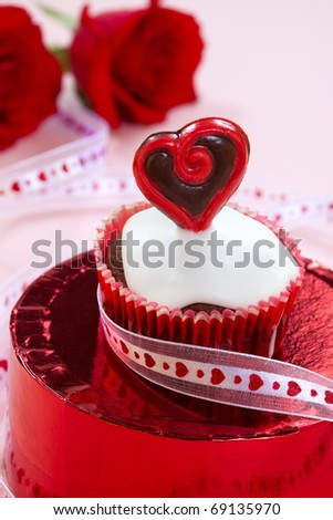 Closeup of Valentine day chocolate cupcakes garnished with heart shaped chocolates. Red roses and gift in background. - stock photo