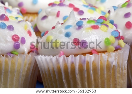 Closeup of vanilla cupcakes with white frosting and rainbow sprinkles - stock photo