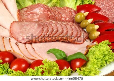 Closeup of various sliced sausages, ham and garnish vegetables - stock photo