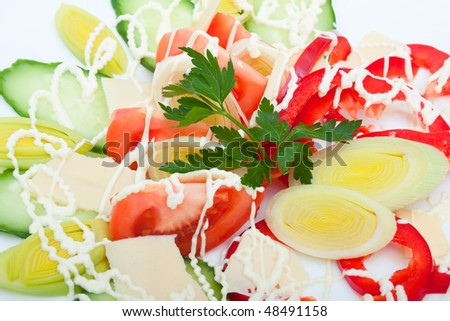 closeup of vegetable salad with cheese on a white plate, focus on the parsley and onion leeks