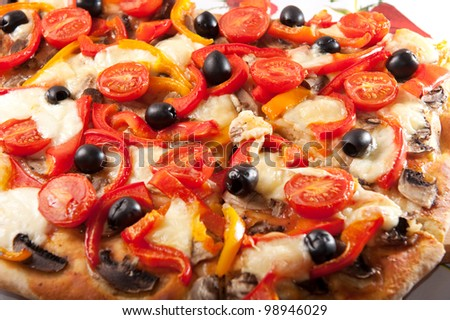 Closeup of vegetarian pizza with mozzarella, pepper, olive and cherry tomatoes
