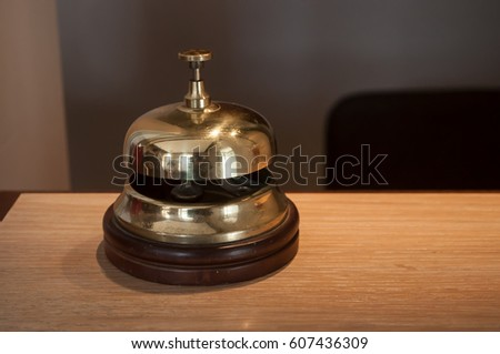 closeup of vintage luxury hotel reception counter desk with golden bell
