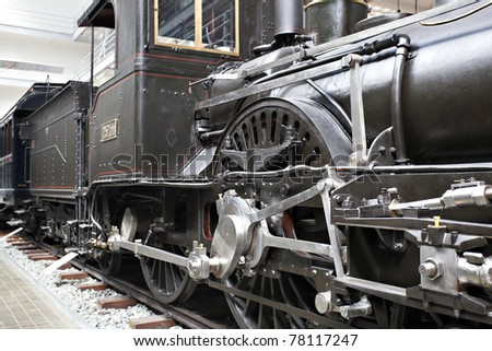 Closeup of vintage steam engine's black, iron wheel - stock photo