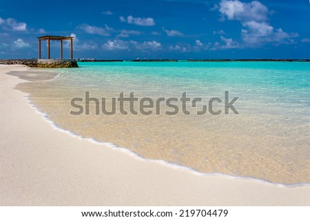 Closeup of water at Maldives with a gazebo in the background - stock photo