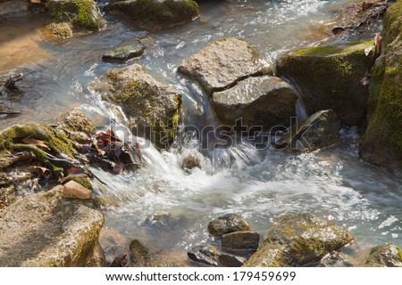 Closeup of water flowing over rocks in a stream.