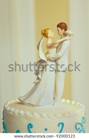 Closeup of wedding cake top bride and groom figurines - stock photo