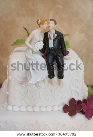 Closeup of wedding cake topper figurines at reception - stock photo