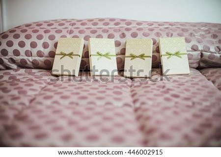 Closeup of wedding invitations with a green ribbon - stock photo