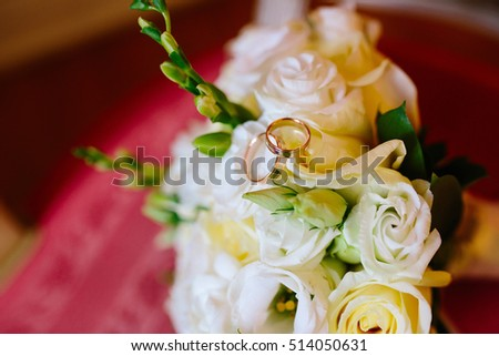 Closeup of wedding rings on the bouquet