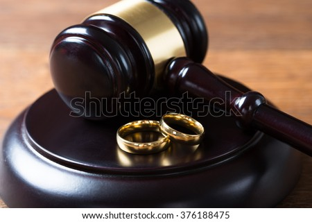Closeup of wedding rings on wooden mallet at table in courtroom - stock photo