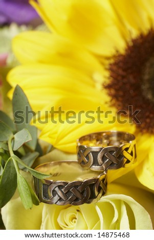 Closeup of wedding rings on yellow sunflower and rose