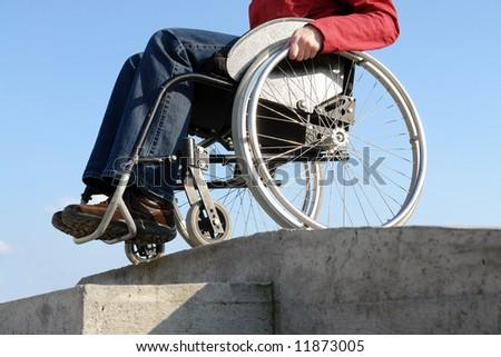 Closeup of wheelchair woman going down the concrete kerb - stock photo