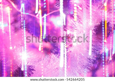 Closeup of white bauble hanging from a decorated Christmas tree with bokeh, copy space, Xmas holiday background.