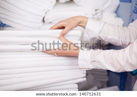 Closeup of white bedsheets stacked in store room of hotel - stock photo