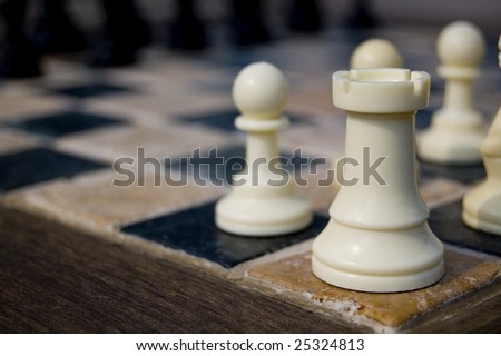 Closeup of white chess rook on tile game board with wood trim.