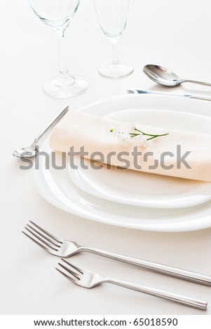 closeup of white place setting with plates forks glasses beige napkin and little flower - stock photo