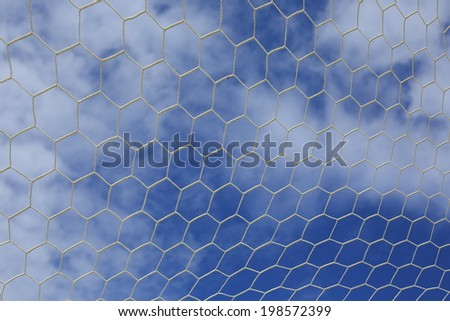 Closeup of white soccer net over blue sky and white cloud  - stock photo