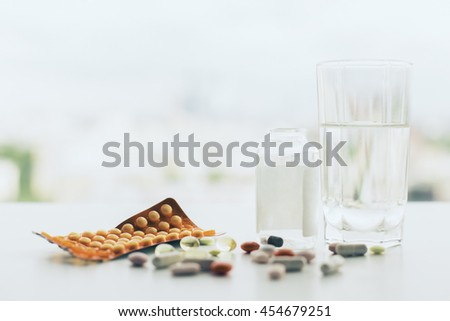 Closeup of white tabletop with different pills, glass of water, medicine bottle and package - stock photo