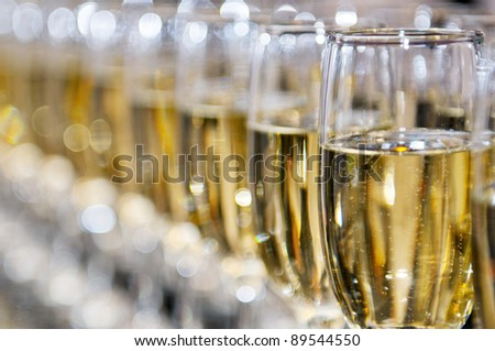 Closeup of white wine glasses in a row on a table - stock photo