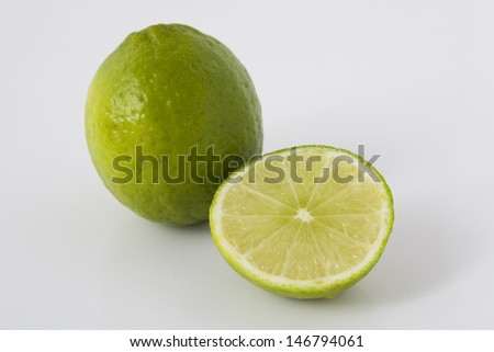 Closeup of whole and sliced limes on light surface