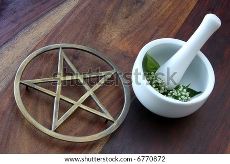 closeup of wicca spell tools and book of shadows with mortar and pestle