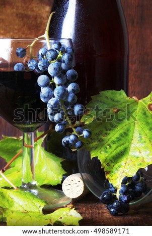 Closeup of wine and grape vine on wood.