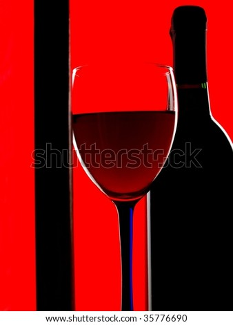 Closeup of  wine bottle and a wine glass framed on a red background.