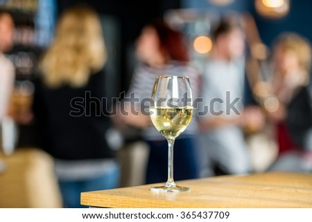 Closeup of wineglass on table at bar with friends in background - stock photo