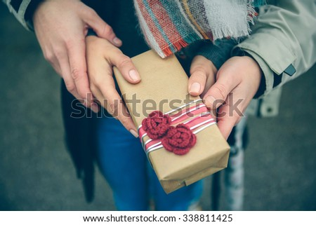 Closeup of woman and man hands showing a gift box with red handmade flowers outdoors in a cold autumn day. Love and couple relationships concept. - stock photo