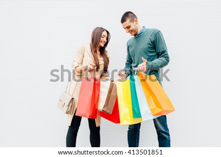 Closeup of woman and man holding colorful shopping bags