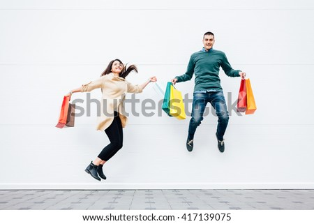 Closeup of woman and man jumping with shopping bags - stock photo