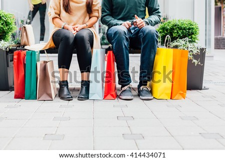 Closeup of woman and man on the bench with colorful shopping bags - stock photo