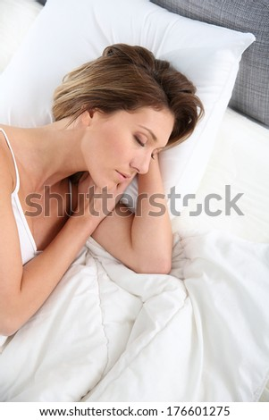 Closeup of woman asleep in bed - stock photo