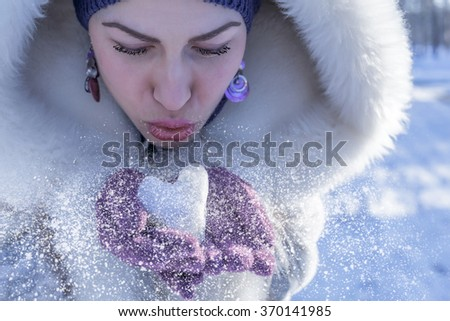 Closeup of woman blowing heart shaped snow